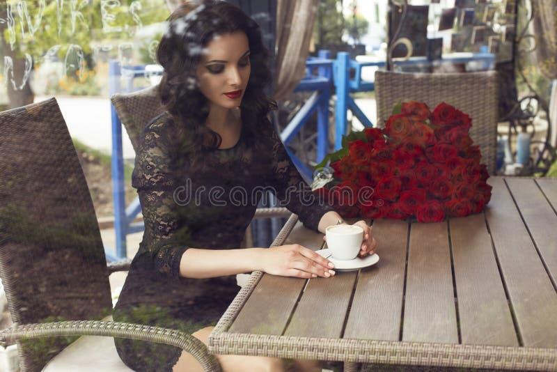 красивое брюнет сидя в кафе города с чашкой кофе стоковые изображения