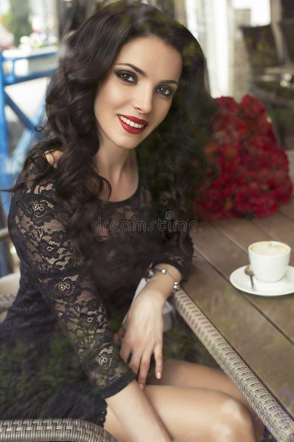 Красивое брюнет сидя в кафе города с чашкой кофе стоковое фото