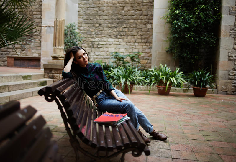 Красивое брюнет сидя на стенде и ждать ее парня стоковая фотография rf