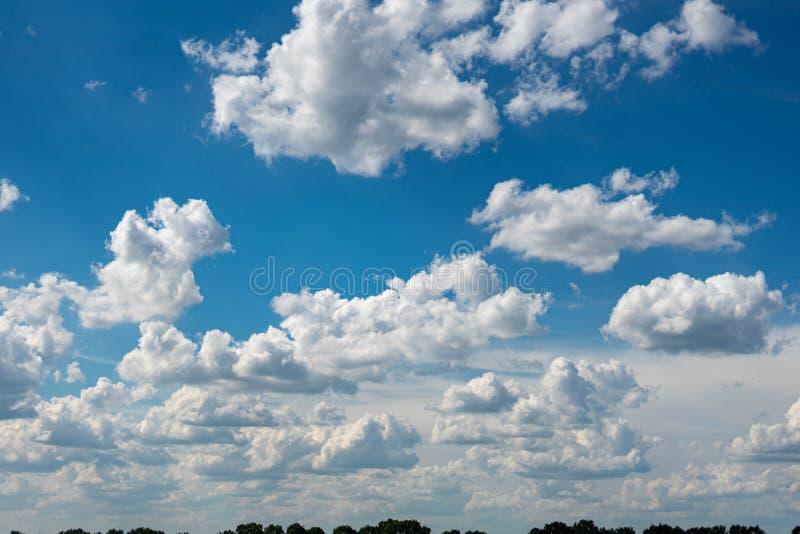 Красивое голубое небо с белыми облаками и тонкой линией горизонта Лучи солнце выходят сквозь отверстие облака стоковые изображения