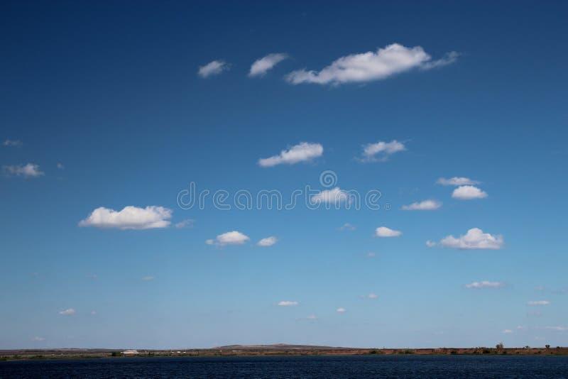 Красивое голубое небо с редкими белыми облаками на солнечный день стоковое изображение
