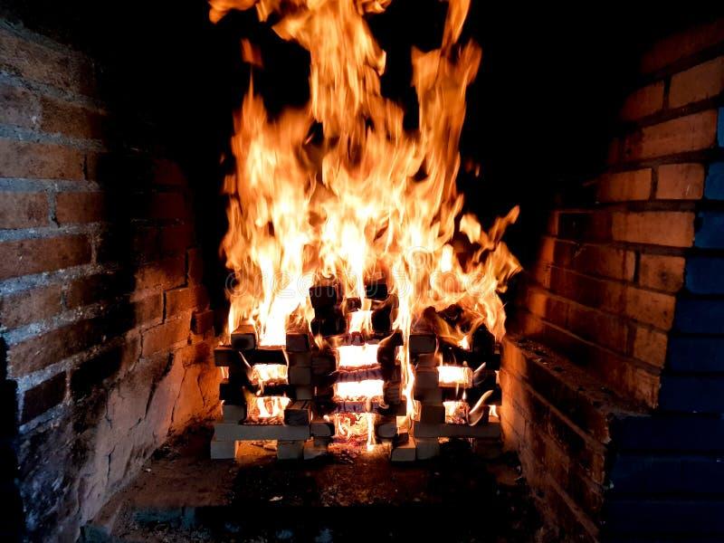 Красивое изображение двигая огня в костре сделанном с деревянными планками в решетке в камине кирпича стоковые фото