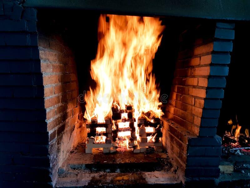Красивое изображение двигая огня в костре сделанном с деревянными планками в решетке в камине кирпича стоковые изображения rf
