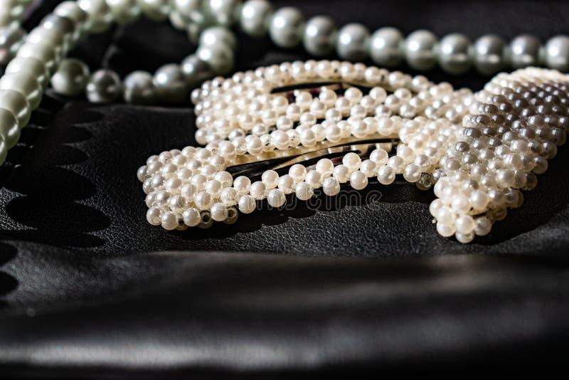 Красивое и модное украшение белых шариков жемчугов, славный milky цвет, на черной кожаной предпосылке стоковые изображения