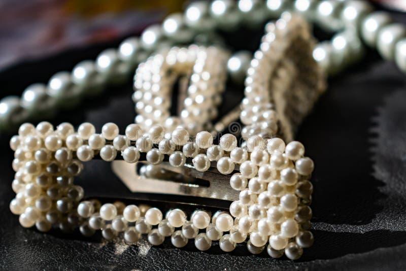 Красивое и модное украшение белых шариков жемчугов, славный milky цвет, на черной кожаной предпосылке стоковая фотография rf