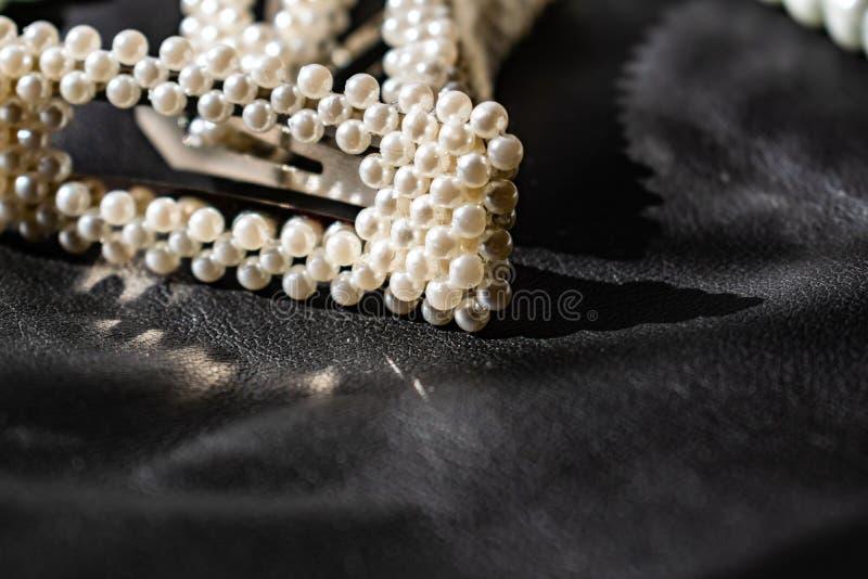 Красивое и модное украшение белых шариков жемчугов, славный milky цвет, на черной кожаной предпосылке стоковое изображение rf
