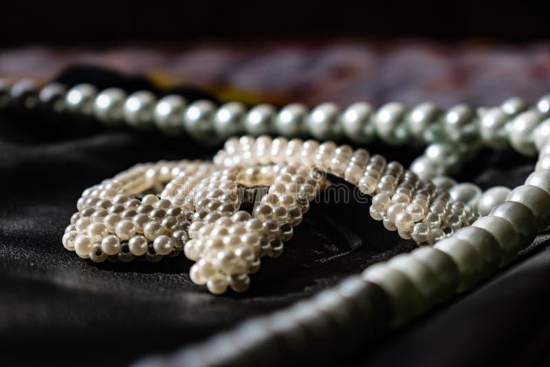 Красивое и модное украшение белых шариков жемчугов, славный milky цвет, на черной кожаной предпосылке стоковые изображения rf