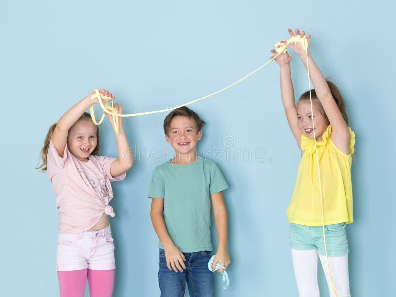 2 красивое и смешные девушки и один крутой мальчик играя с много шламом перед голубой предпосылкой и имея много потеху стоковые фото