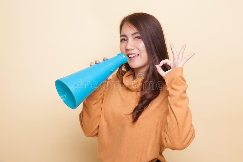 Красивое молодое азиатское О'КЕЙ выставки женщины объявляет с мегафоном стоковые фотографии rf