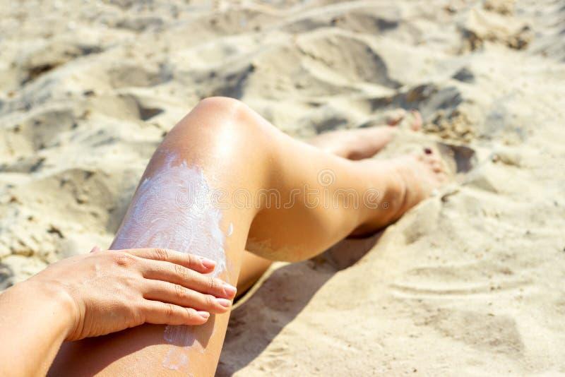 Красивое молодое женское, прикладывающ сливк suntan на пляже стоковое фото