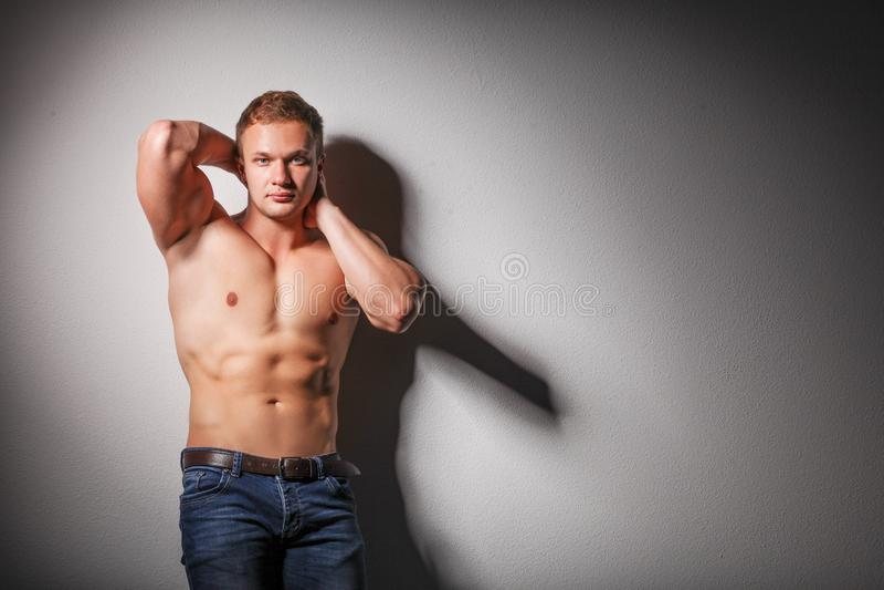 Красивое молодое мышечное без рубашки положение молодого человека стоковые изображения rf