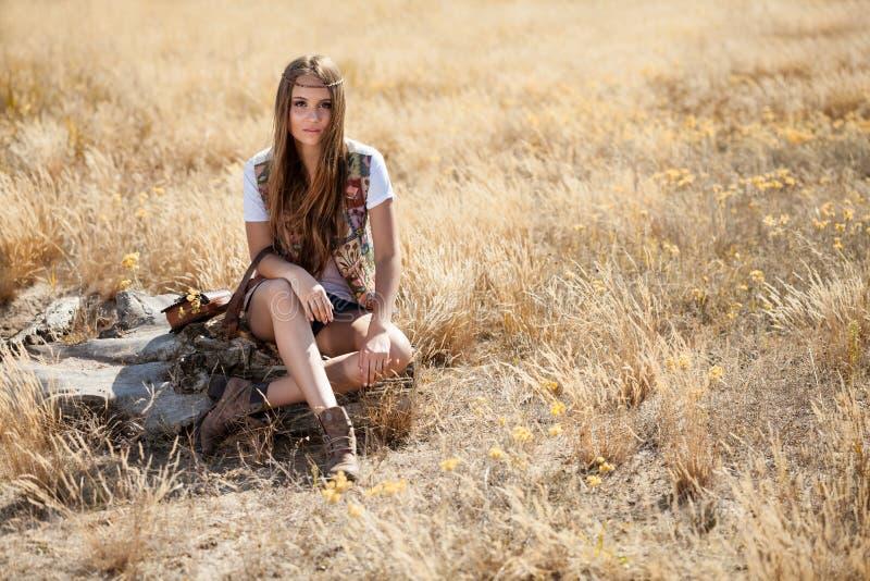 Красивое модельное усаживание на пне в поле на восходе солнца стоковое фото