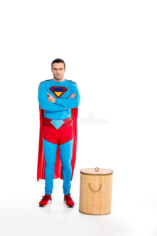 красивое мужское положение супергероя с пересеченными оружиями около корзины прачечной и смотреть камеру стоковые изображения rf