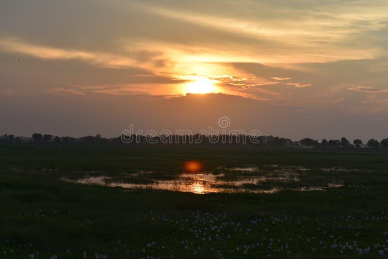 Красивое небо захода солнца, отраженное водой в озере стоковые фотографии rf