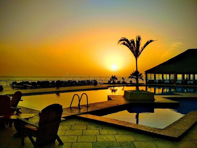 Красивое небо poolside и захода солнца в Сенегале, Африке Роскошный тропический ландшафт пляжа с ладонями, шезлонгами и loungers  стоковая фотография