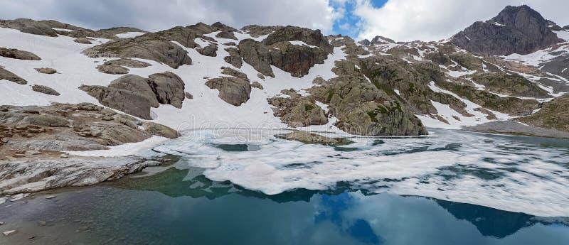 Красивое озеро высокой горы во французских Альп с водой бирюзы и покрытых со снегом в некоторых местах стоковая фотография rf