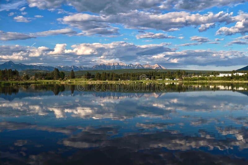 Красивое отражение маленькой деревни и гор в спокойной воде на летний день стоковое фото