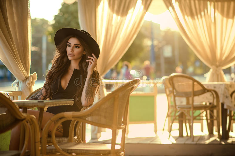 Красивое очарование татуировало брюнет в меньших черном платье и ультрамодной шляпе fedora сидя в славном под открытым небом рест стоковая фотография rf
