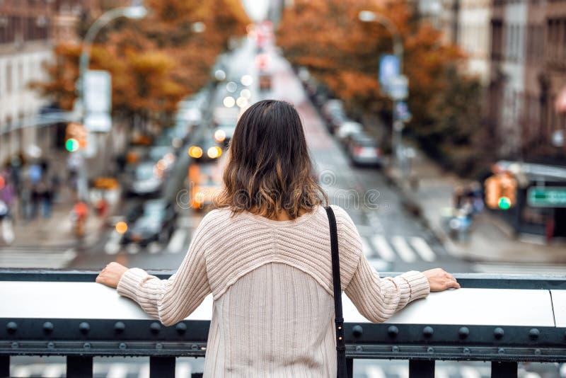 Красивое перемещение женщины и смотреть улицу Нью-Йорка с автомобильным движением и желтые деревья на времени осени от высокой то стоковое изображение rf