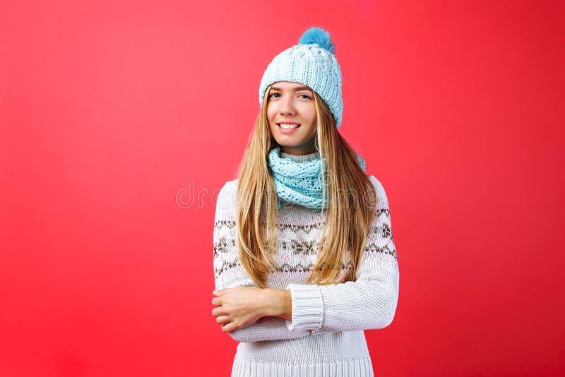 Красивое положение девушки изолированное на красной предпосылке, в теплой голубой шляпе и теплом шарфе стоковое изображение