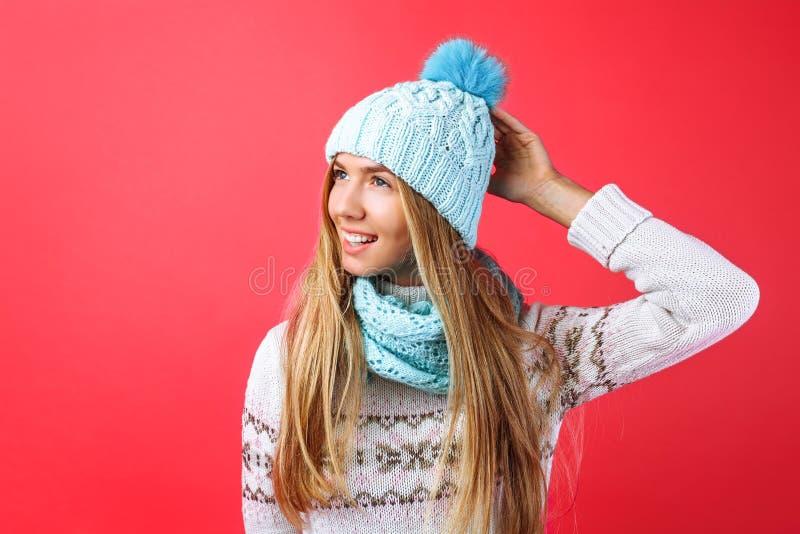Красивое положение девушки изолированное на красной предпосылке, в теплой голубой шляпе и теплом шарфе стоковая фотография rf