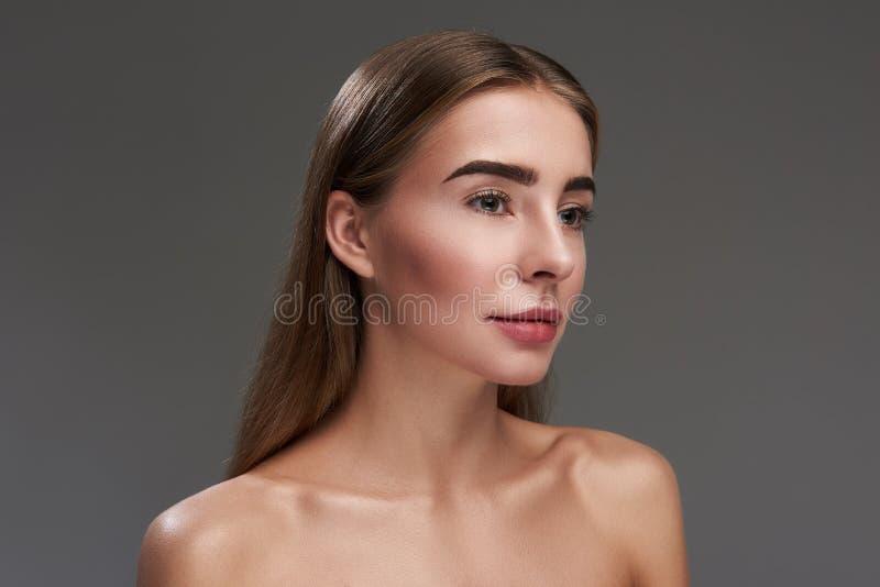 Красивое положение молодой женщины против серой предпосылки стоковое изображение