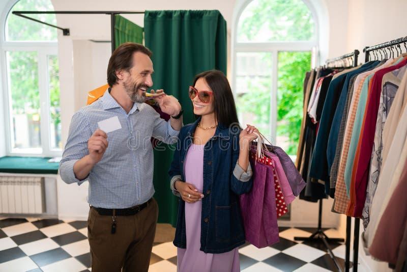 Красивое положение пар в магазине одежды с пакетами стоковое фото