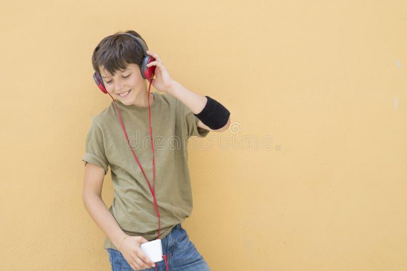 Красивое предназначенное для подростков носящ зеленую футболку слушая к музыке стоковое фото