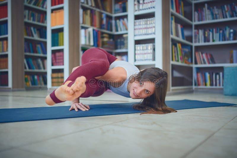 Красивое представление Ashtavakrasana asana йоги handstand практик женщины в библиотеку стоковое фото