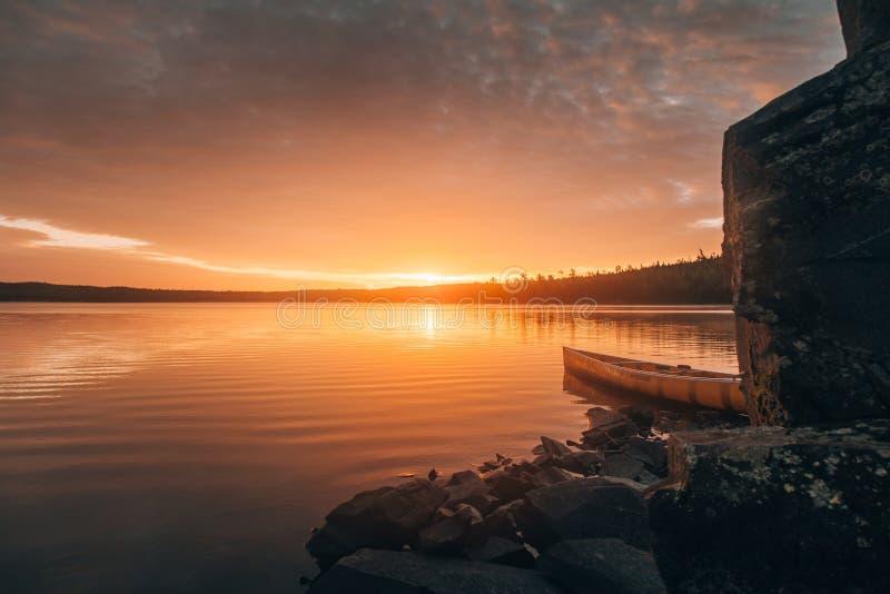 Красивое рискованное предприятие каноэ на озере около каменных холмов во время захода солнца стоковая фотография rf