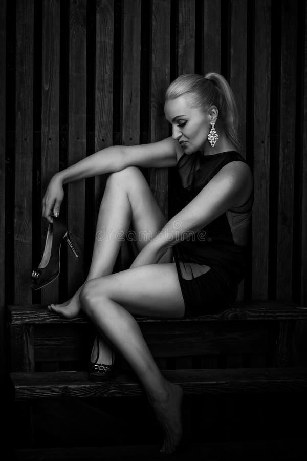 Красивое сексуальное белокурое платье черноты женщины вкратце стоковая фотография