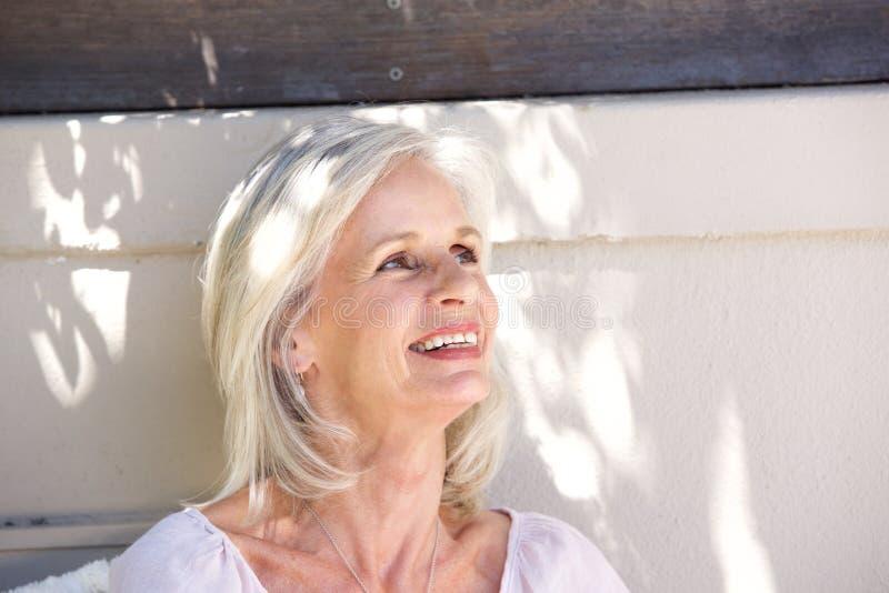 Красивое снаружи более старой женщины усмехаясь смотря ослабленный стоковые фотографии rf