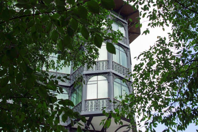 Красивое старое здание с балконом и серией окон на угле улицы в городке Тбилиси старом, зелеными цветами листвы, стоковое изображение
