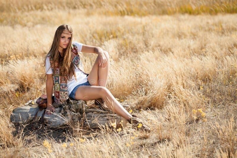 Красивое усаживание молодой дамы модельное на пне в поле на восходе солнца стоковое фото rf