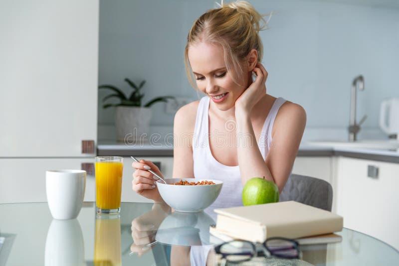 красивое усмехаясь muesli еды молодой женщины на завтрак стоковые изображения rf