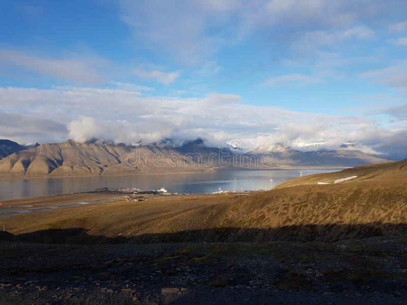 Красивое фото обзора частей longyear аэропорта города с могущественными горами и морем стоковое фото rf