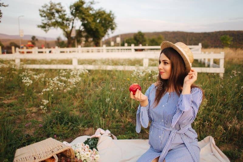 Красивое шоу беременной женщины и съесть красное яблоко E r Счастливая улыбка женщины стоковое изображение