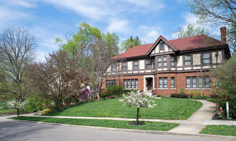 Красиво благоустраиванный дом Tudor английского языка весной стоковое фото