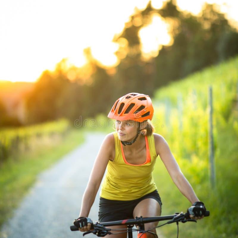 Красиво, молодая женщина катается на горном велосипеде стоковое изображение rf