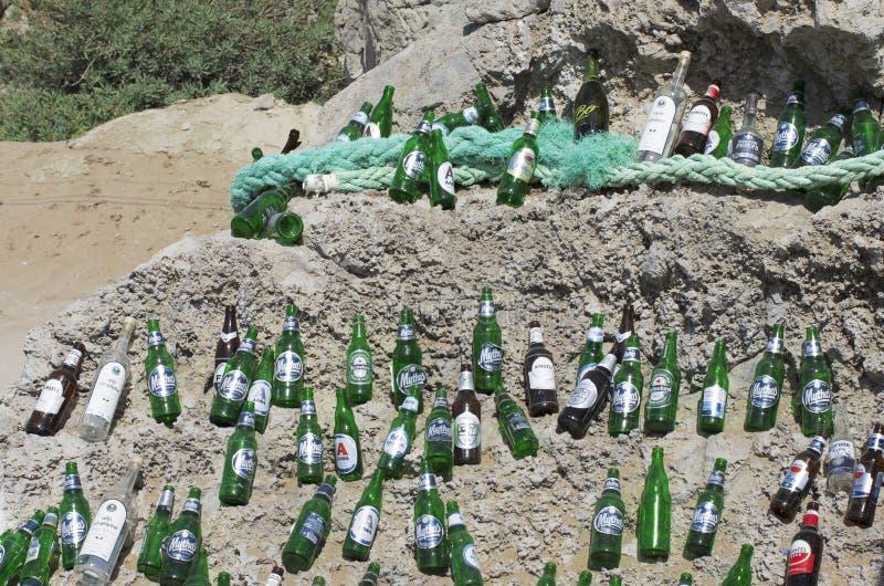 Красиво положенные вне пустые пивные бутылки на огромном валуне в солнечной погоде стоковая фотография