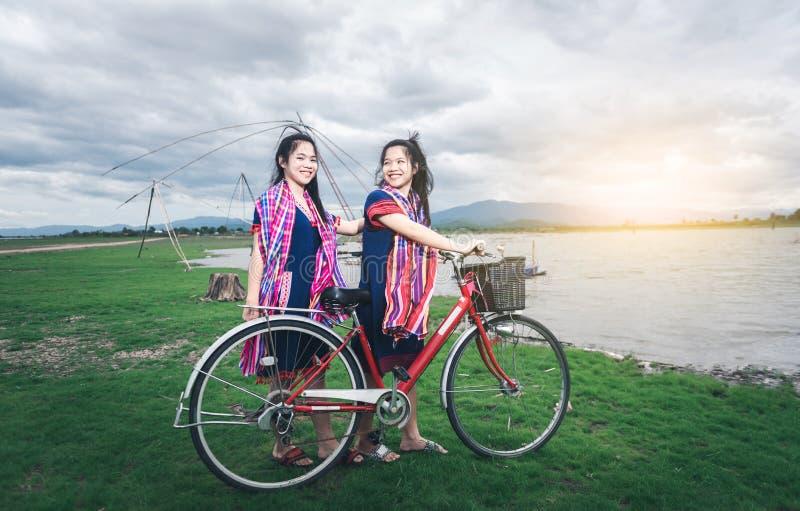 Красивые азиатские девушки наслаждаются перемещением путем ехать на велосипеде стоковое фото