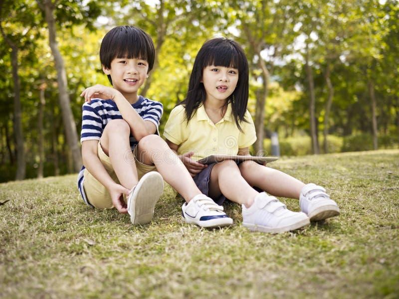 Красивые азиатские дети сидя на траве стоковое фото rf