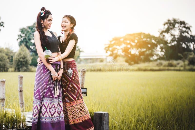 Красивые азиатские женщины в местном положении платья и насладиться е стоковая фотография