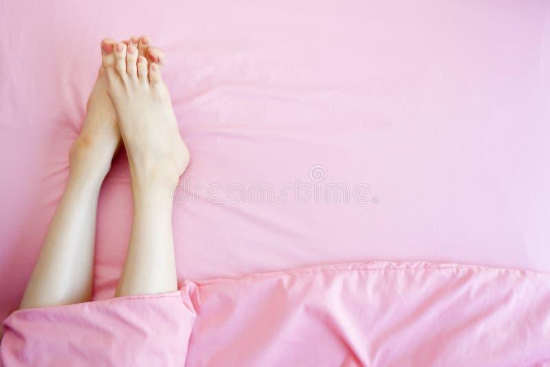 Красивые азиатские ноги и ноги тела молодой женщины изолированные на пастельной розовой предпосылке спальни Женская нога во сне к стоковые изображения rf