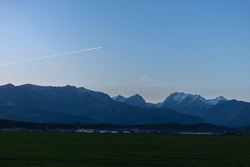 Красивые Альп над зеленым ландшафтом вечера поля стоковые фото