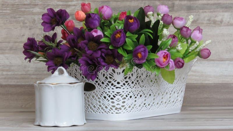 Красивые белые пластичные корзина и искусственные цветки стоковые фотографии rf