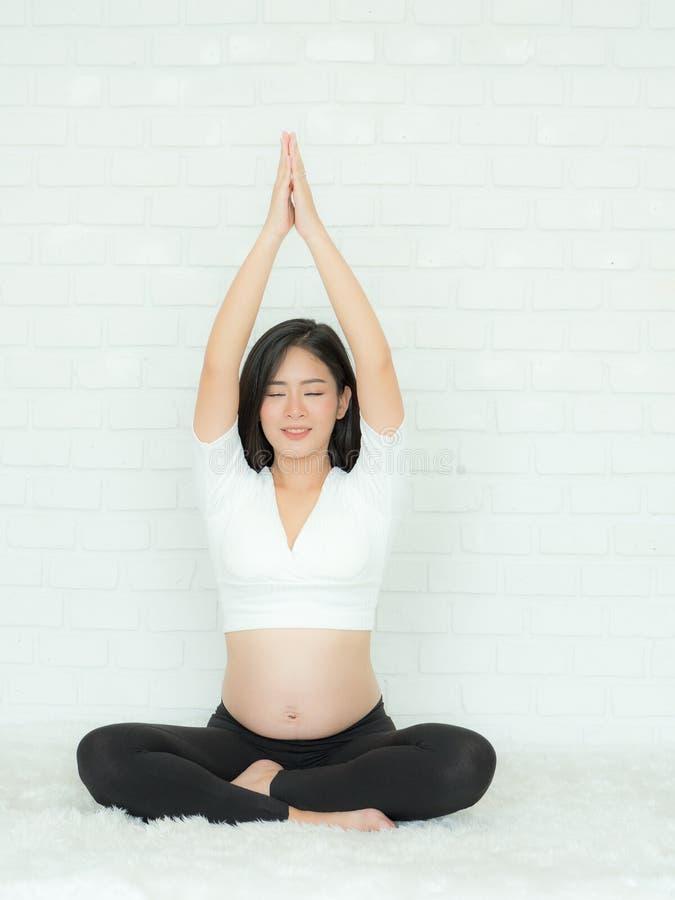 Красивые беременные женщины сидят на кровати и ослабляют с тренировкой стоковое изображение rf
