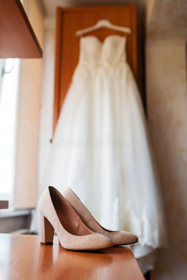 Красивые белые bridal ботинки и платье на роскошной спальне стоковые фотографии rf