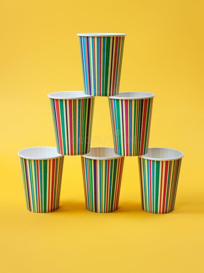 Красивые бумажные стаканчики штабелированные в пирамиде желтый цвет предпосылки яркий minimalism стоковое изображение rf