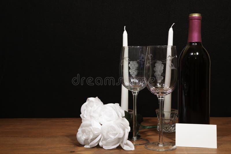 Красивые вытравленные бокалы и бутылка красного вина, белых свечей и белых роз на деревянном столе с биркой имени на темноте стоковое изображение